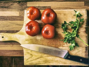 Tomatoes, herbs, and knife on a cutting board