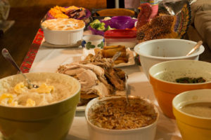 table set with various dishes of food and Thanksgiving decorations