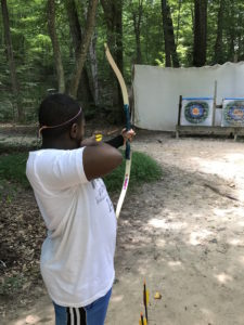 child aiming bow and arrow at outdoor archery target