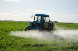 tractor spraying pesticide in field