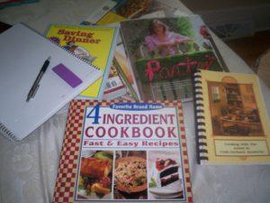 multiple cookbooks, savings guide, notebook, and pen