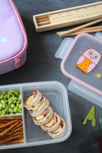 Purple lunch box, pinwheel sandwich, pretzel sticks, beans, a pencil box and ruler,