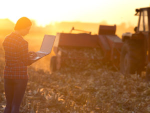 farm machinery and a woman in a field using laptop computer