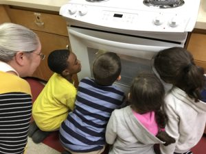 children looking into oven window as adult looks in over their shoulders