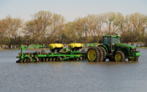 Tractor with plow and fertililzer attachments sitting in flooded field