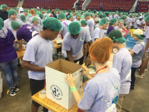 Large group of 4-H youth volunteers filling food boxes