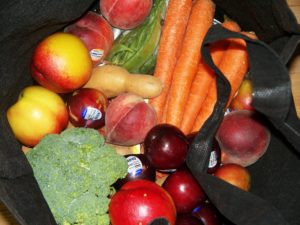 assorted fruit and vegetables in black shopping bag