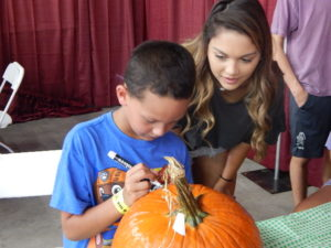 Youth volunteer helping child decorate pumpkin at fair
