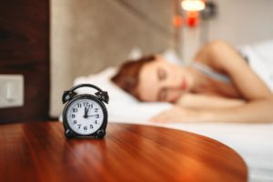 alarm clock on table with woman sleeping in background