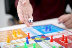 man rolling dice on board game