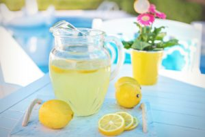Pitcher of lemonade withlemons around pitcher