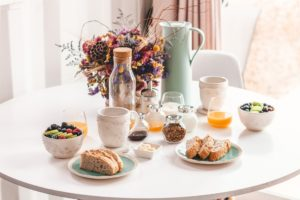 various breakfast foods on table with flowers