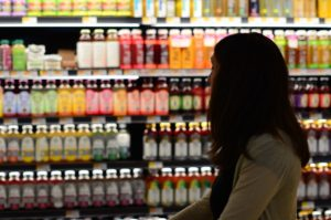 woman looking at items on grocery store shelf