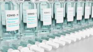 clear bottles with writing that say COVID-19 vaccine